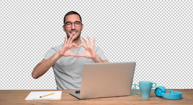 Jovem feliz fazendo um gesto de amor sentado em sua mesa