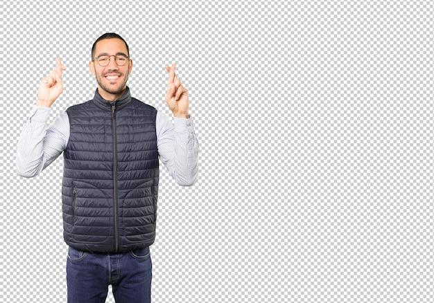Jovem feliz, fazendo um gesto de dedos cruzados