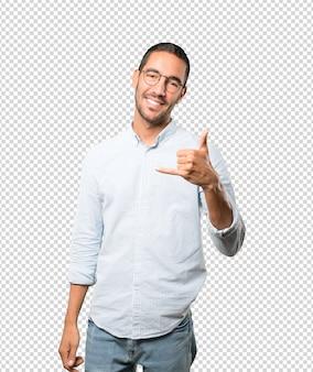Jovem feliz, fazendo um gesto de ligar com a mão