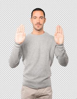Jovem feliz fazendo um gesto de parar com a palma da mão