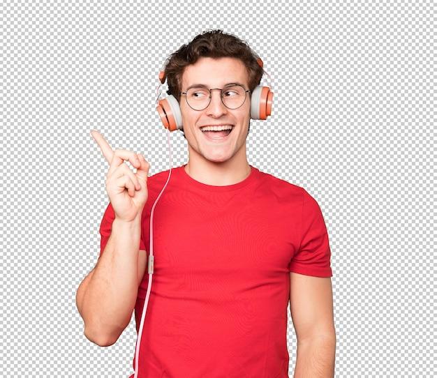 Jovem feliz usando fones de ouvido e um smartphone e apontando para cima