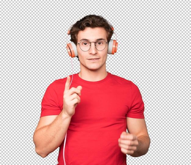 Jovem feliz usando fones de ouvido e um smartphone e apontando para você