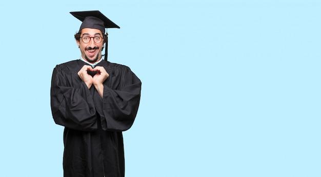 Jovem graduado de pé para os lados, sorrindo, olhando feliz e apaixonado