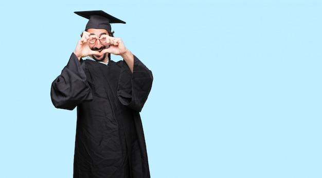 Jovem graduado sorrindo, olhando feliz e apaixonado, fazendo a forma de um coração com as mãos.