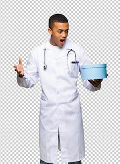 Jovem, homem americano afro, doutor, segurando, caixa presente, em, mãos
