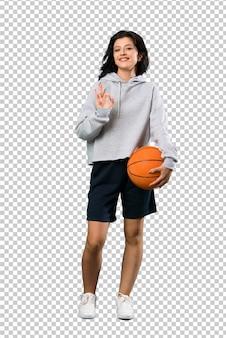 Jovem jogando basquete mostrando sinal de ok com os dedos