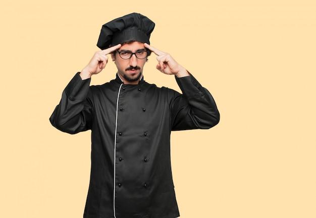 Jovem louco como chef concentrando-se duro em uma idéia, com um olhar sério