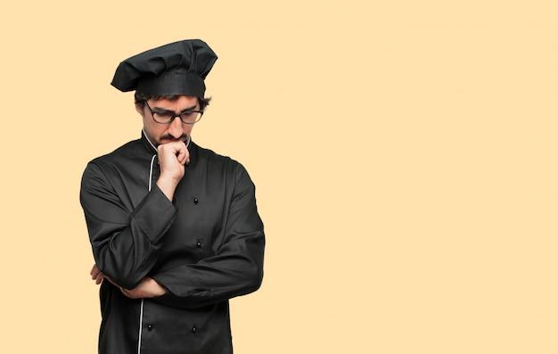 Jovem louco como um chef com um olhar confuso e pensativo, olhando de soslaio