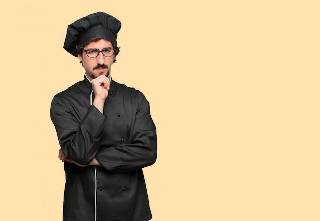Jovem louco como um chef com um olhar confuso e pensativo