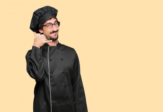Jovem louco como um chef fazendo um gesto de telefonema ou sinal, com um olhar orgulhoso, feliz e satisfeito