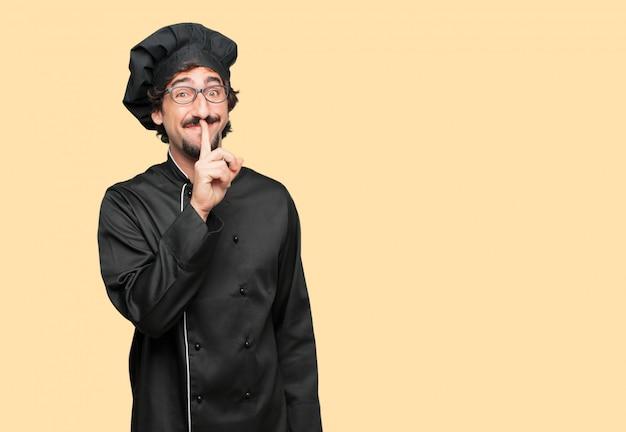Jovem louco como um chef sorrindo, com o dedo indicador na frente da boca, pedindo silêncio ou partilha