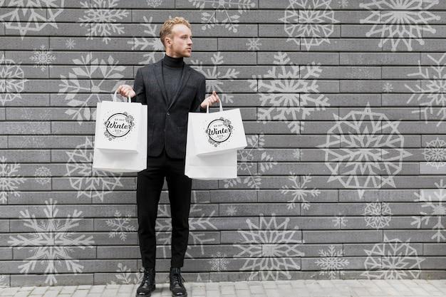 Jovem macho segurando sacolas de compras