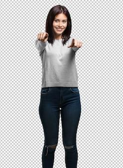 Jovem mulher bonita alegre e sorridente apontando para a frente