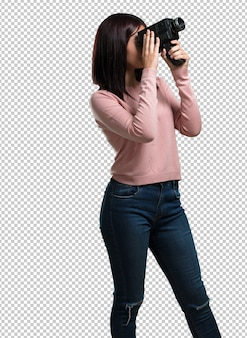 Jovem mulher bonita animada e divertida, olhando através de uma câmera de filme, procurando uma foto interessante, gravando um filme, produtor executivo