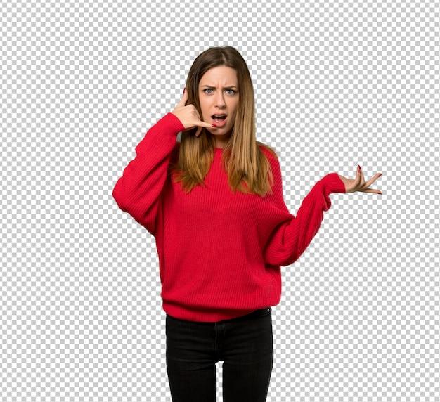 Jovem mulher com camisola vermelha, fazendo gesto de telefone e duvidando