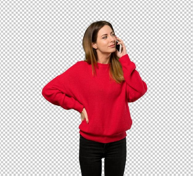Jovem mulher com camisola vermelha, mantendo uma conversa com o telefone móvel
