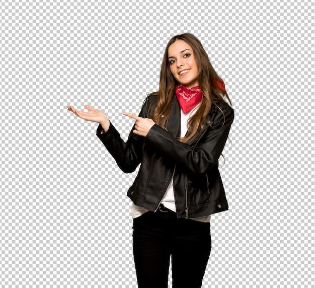 Jovem mulher com casaco de cabedal segurando copyspace imaginário na palma da mão para inserir um anúncio