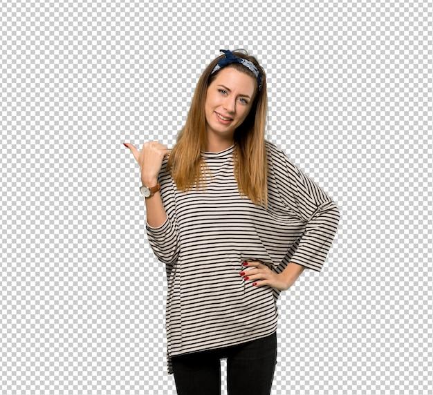 Jovem mulher com lenço na cabeça apontando para o lado para apresentar um produto
