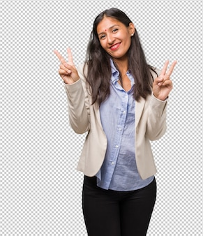 Jovem mulher de negócios indiano divertido e feliz, positivo e natural, fazendo um gesto de vitória, paz