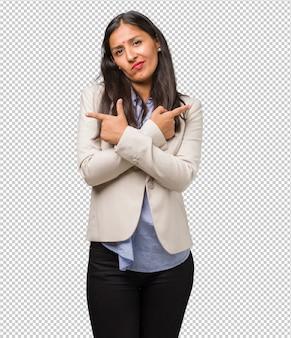 Jovem mulher indiana de negócios confuso e duvidoso, decidir entre duas opções, conceito de indecisão