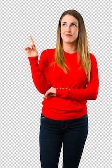 Jovem mulher loira apontando com o dedo indicador uma ótima idéia