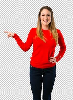 Jovem mulher loira apontando o dedo para o lado e apresentando um produto