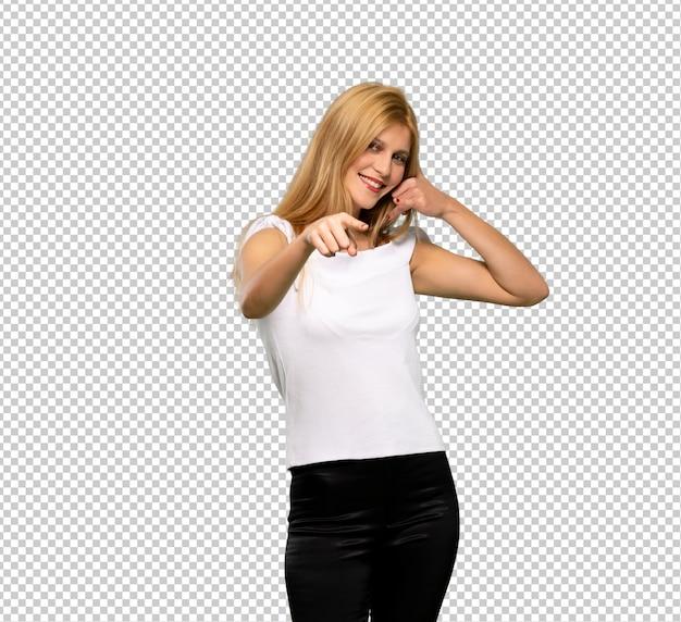 Jovem mulher loira fazendo gesto de telefone e apontando a frente