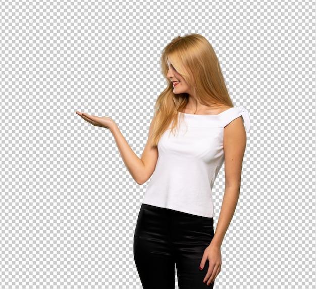 Jovem mulher loira segurando copyspace imaginário na palma da mão para inserir um anúncio