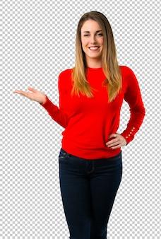 Jovem mulher loira segurando copyspace imaginário na palma da mão