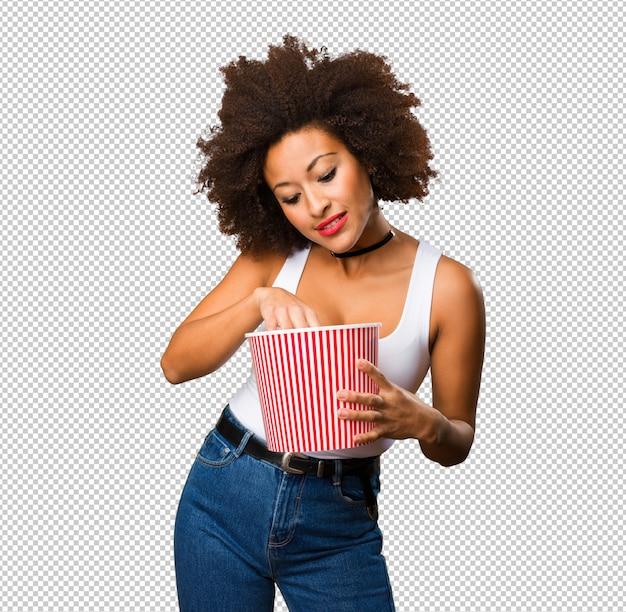 Jovem mulher negra segurando um balde de pipoca