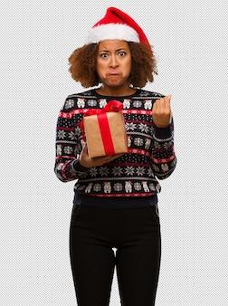 Jovem mulher negra segurando um presente no dia de natal, fazendo um gesto de necessidade