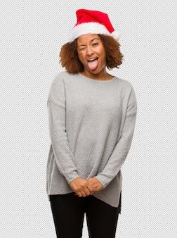 Jovem mulher negra vestindo um chapéu de papai noel funnny e amigável mostrando a língua
