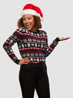 Jovem, mulher preta, em, um, trendy, natal, suéter, com, impressão, segurando, algo, com, mão