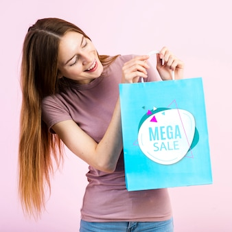 Jovem mulher segurando um saco de papel a sorrir