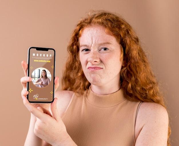 Jovem mulher segurando uma maquete de smartphone
