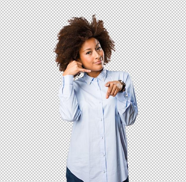 Jovem negra fazendo gesto de telefone