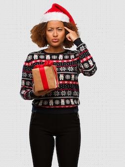 Jovem negra segurando um presente no dia de natal, fazendo um gesto de concentração