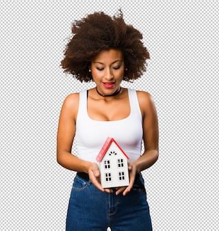 Jovem negra segurando uma pequena casa