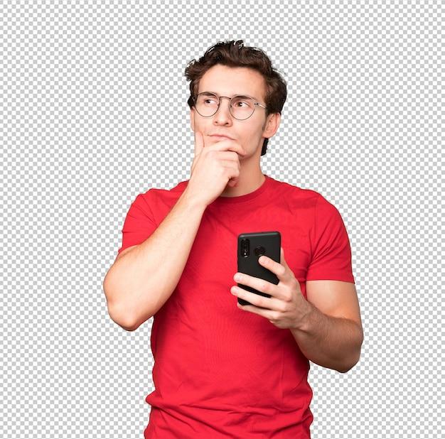 Jovem pensativo usando seu telefone celular