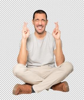 Jovem preocupado fazendo um gesto de dedos cruzados