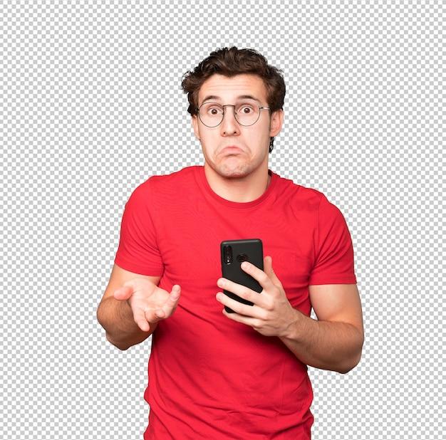 Jovem preocupado segurando um smartphone e fazendo um gesto de dúvida