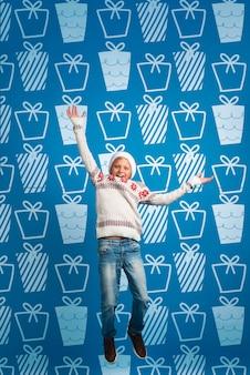 Jovem rapaz vestido camisola temática de natal pulando