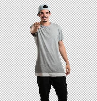 Jovem rapper homem alegre e sorridente apontando para a frente