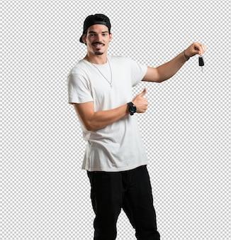 Jovem rapper homem feliz e sorridente, segurando as chaves do carro, confiante