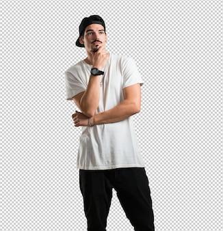 Jovem rapper homem pensando e olhando para cima, confuso sobre uma idéia, estaria tentando encontrar uma solução