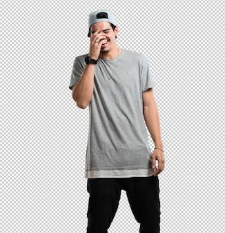 Jovem rapper homem rindo e se divertindo, sendo relaxado e alegre, se sente confiante e bem sucedido