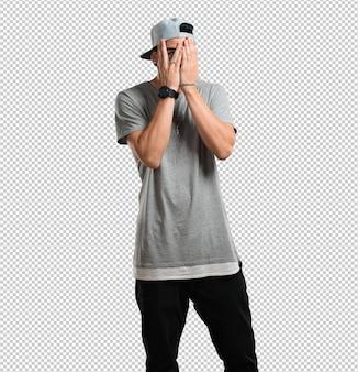 Jovem rapper homem sente-se preocupado e assustado, olhando e cobrindo o rosto, conceito de medo e ansiedade