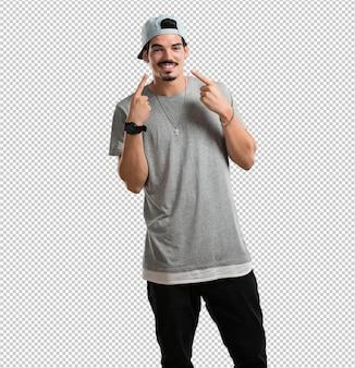 Jovem rapper homem sorri, apontando a boca, conceito de dentes perfeitos, dentes brancos, tem uma atitude alegre e jovial