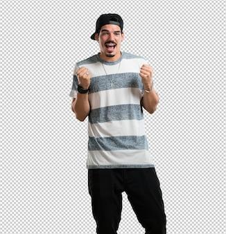 Jovem rapper muito feliz e animado, levantando os braços, comemorando uma vitória ou sucesso