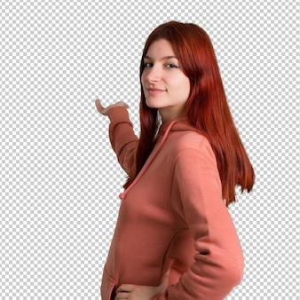 Jovem ruiva com blusa rosa apontando para trás com o dedo indicador apresentando um produto